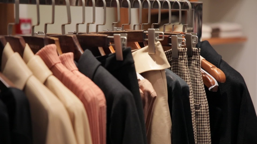 On the hangers are a lot of clothes of various colors. An assortment of clothing in a store. Panorama of dresses, jackets, shirts, skirts and other clothes Royalty-Free Stock Footage #1054307594