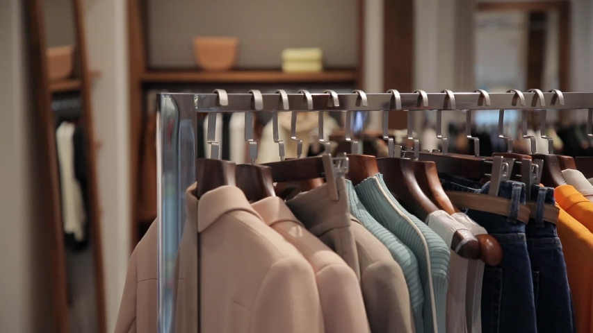 On the hangers are a lot of clothes of various colors. An assortment of women's clothing in a store. Panorama of dresses, jackets, shirts, skirts and other clothes Royalty-Free Stock Footage #1054307600