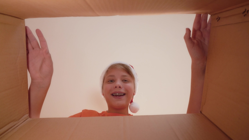 Closeup view video of two curious eyes of young kid looking inside of closed cardboard box through gap than boy opens carton package happily and smiling. Boy happy with his unexpected Christmas gift.