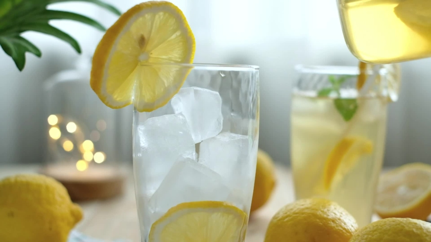 Healthy iced lemon drink for detoxification poured in glasses. Iced lemon drink is a healthy beverage for detoxification. Some might drink lemon infused water with gin for cocktail.  Pouring concept. | Shutterstock HD Video #1054310009