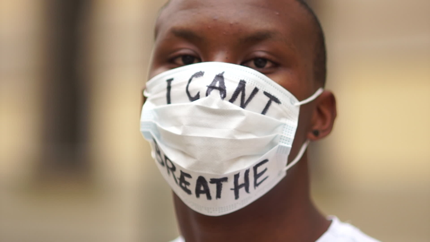 Black lives matter, mass protests against racism in the USA and Europe. Outdoor portrait of a African American in a medical mask with the inscription I cant breathe