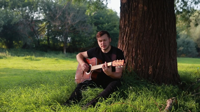A guy in a black T-shirt sits on the grass under a tree, plays and sings on an acoustic guitar.