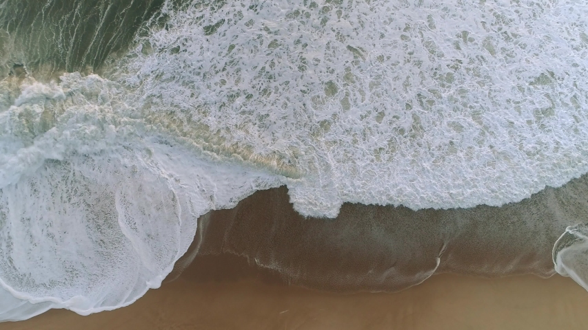 Whitecap waves of sea water washing the sandy beach coast. Wet sand and salty sea air. Aerial top down shot, 4K | Shutterstock HD Video #1054311746