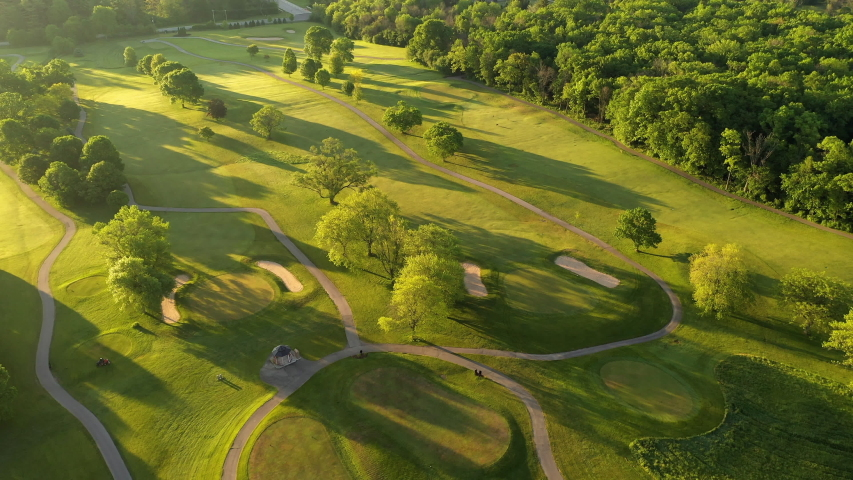 Aerial view of Golf course. Establishing shot, drone flying over golf club. Early morning, summertime, sunlight Royalty-Free Stock Footage #1054312301