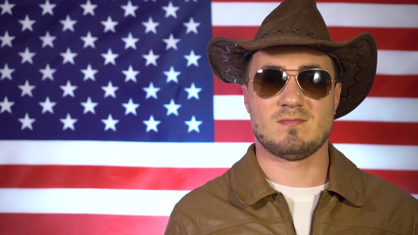 Portrait of a smiling man in a cowboy hat, leather jacket and sunglasses on the background of the American flag, a man shows a peace sign.