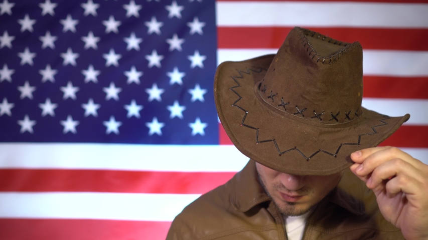 Portrait of a serious man in a cowboy hat, a leather jacket on the background of the American flag, a man raises his head, holding his hand on his hat.