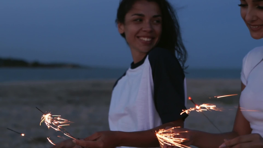 Female friends walking, dancing, having fun at night party at seaside with sparklers in hands. Young teenage women partying on beach with firework, bengal lights. Girls in slow motion, steadycam shot.   Shutterstock HD Video #1054318142