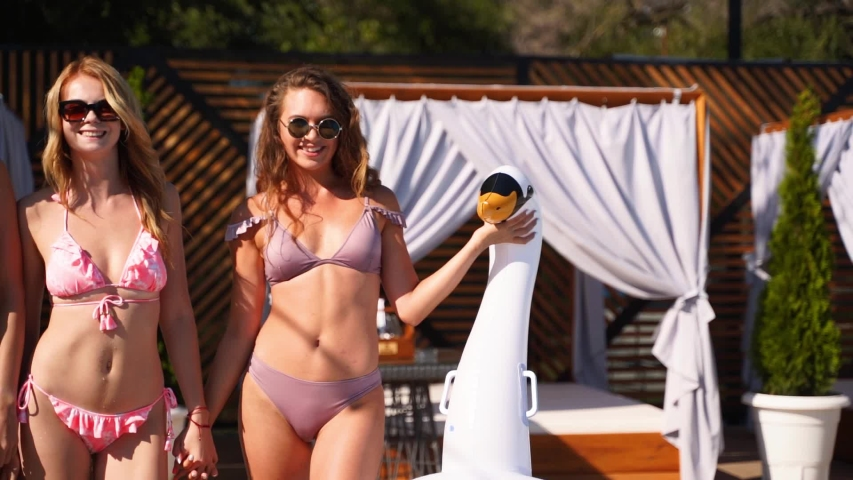 Hot pretty girls in bikini walking together with inflatable swan, swim ring by swimming pool. Attractive fitted women in swimsuits have fun relaxing on sunny day summer party at luxury resort. Slomo