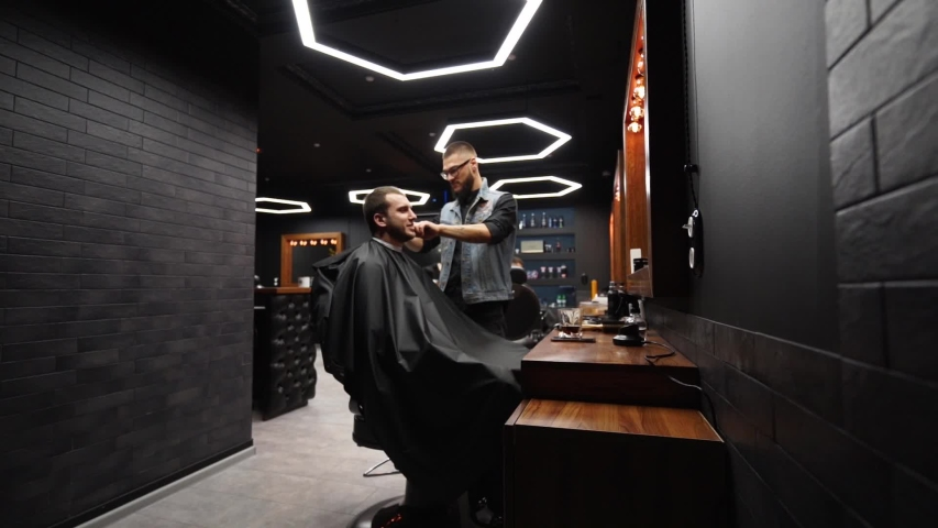 Trendy barber cuts bearded man's hair with a clipper in barbershop. Men's hairstyling and hair cutting in salon. Grooming the hair with trimmer. Hairdresser doing haircut in retro hair salon. Dolly in