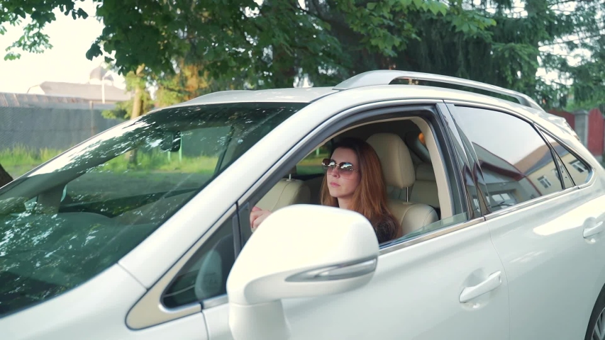 Portrait of a young woman in sunglasses rides in a luxury white car with an open window. The car is in motion. Attractive female with long hair on a background of nature trees