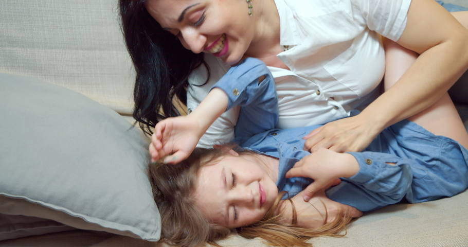 Cheerful family mother and daughter embracing and laughing lying on bed together. Happy young mom tickling her cute little daughter enjoying communication at home.