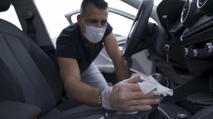 A man disinfects the steering wheel with an antibacterial disinfectant wipe on the Covid-19 quarantine for coronavirus. The man cleans the interior of the car with a cloth and a sprayer. 4k Royalty-Free Stock Footage #1054321280