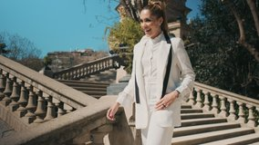 Conceptual shot of young gorgeous woman in classic white suit dreamily running down the stairs outdoor. Elegant businesswoman hurry on meet