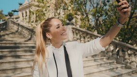 Young elegant cheerful woman happily taking selfie on smartphone on stairs in old city park over beautiful architecture. Attractive lady taking selfie outdoor