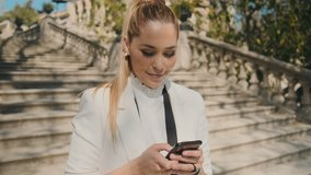 Young gorgeous elegant woman in classic suite happily using messenger on smartphone and sending selfie on stairs in old city park over historical architecture