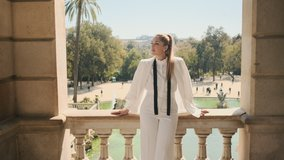 Tracking in shot of gorgeous woman in stylish white suit standing on old balcony with beautiful view on city park