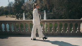 Side view shot of attractive elegant woman in white suit confidently walking through old city park