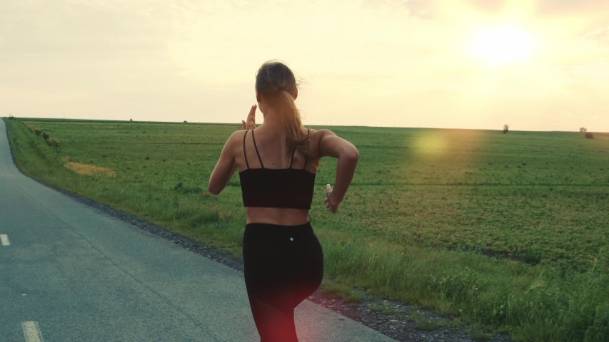 Follow-up Shot of Young Athlete Woman Running Fast down the Road, Training Hard, Getting Ready for Race Competition or Marathon. Fit Girl in Black Sportswear Jogging At Dawn along the Green Fields.