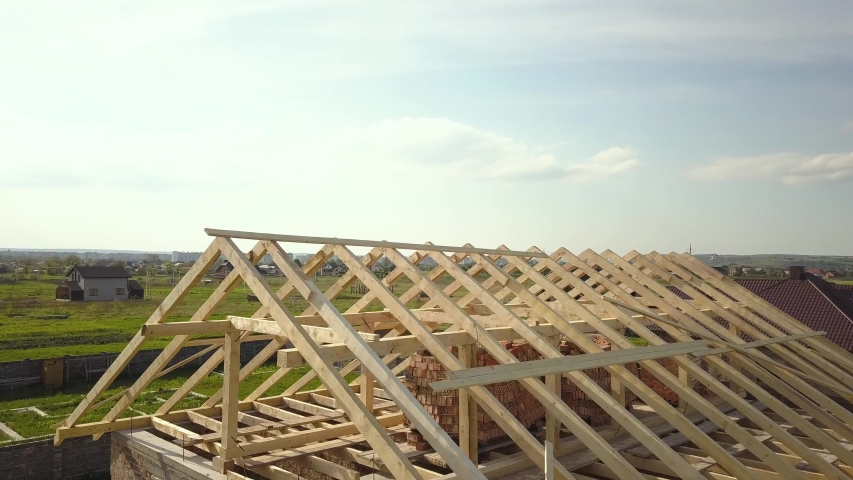 Aerial view of unfinished brick house with wooden roof frame structure under construction. Royalty-Free Stock Footage #1054326242