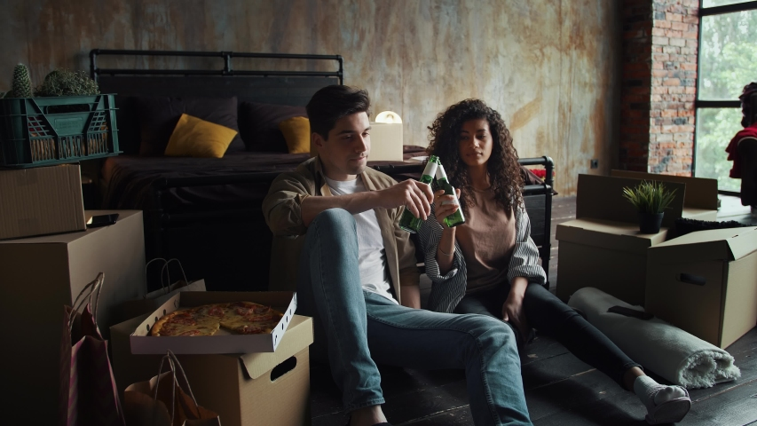 Man and woman relocating to a new flat. Smiling, enjoying beer and pizza. Sitting on floor next to bed. Bedroom with cardboard boxes. Close up | Shutterstock HD Video #1054326344