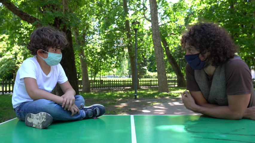 Europe, Italy , Milan - Sad boy with mask  arrives to the park with his father  and the play area is closed and empty of children due COVID19 Coronavirus quarantine home lockdown   Royalty-Free Stock Footage #1054326716