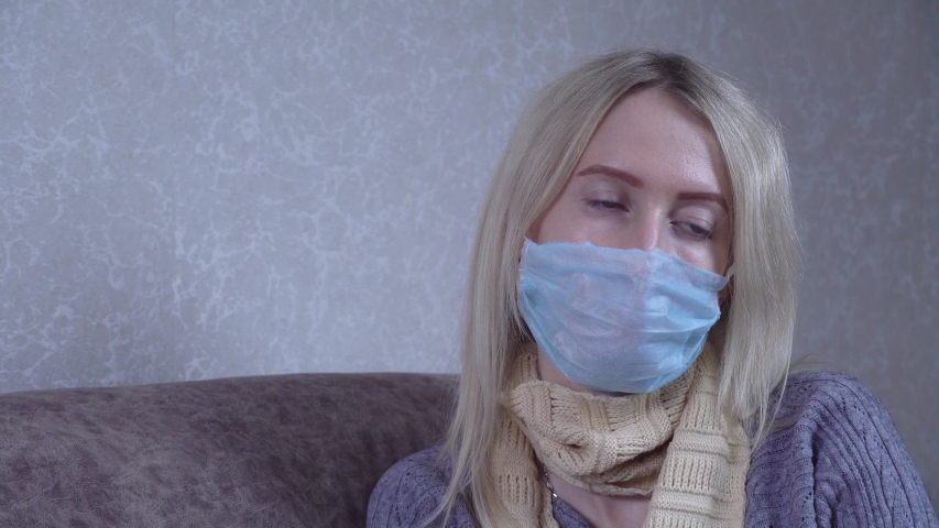 Outbreak of a coronavirus spray from a sore throat. a masked woman who treats a throat with a spray and sprays in her mouth. Home treatment, apartment in the room. | Shutterstock HD Video #1054329839