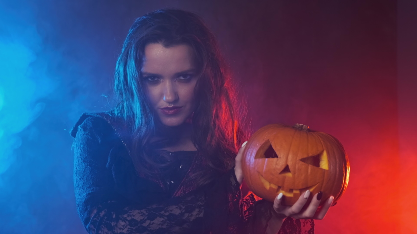 Vampiress holding jack-o-lantern. Smoky background with colored lights. Young witch in black cloak holds pumpkin in her hands. Medium shot in 4K, UHD | Shutterstock HD Video #1054329902