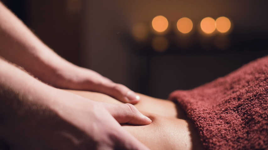 Close-up Young male massage therapist does back massage to a woman with a tattoo in a massage room with dim lights on the background of candles. Low key premium massage concept | Shutterstock HD Video #1054330481