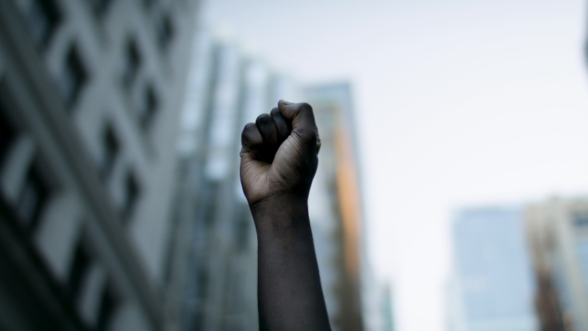 Raised black man's fist in protest. Social justice and peaceful protesting racial injustice.