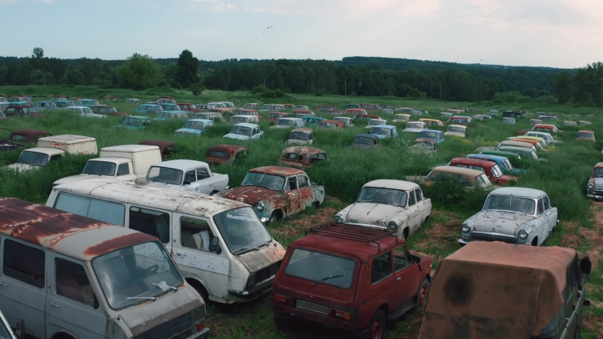 Aerial view of many old retro rusty abandoned cars in green field, vintage cars
