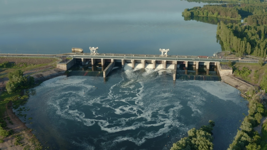 Dam with flowing water through gates. Hydroelectric power station, aerial top view Royalty-Free Stock Footage #1054332164