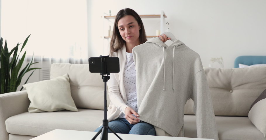 Pretty young female blogger sitting on couch, recording video on camera, sharing shopping experience with followers. Attractive millennial designer presenting clothes, filming advertisement indoors.