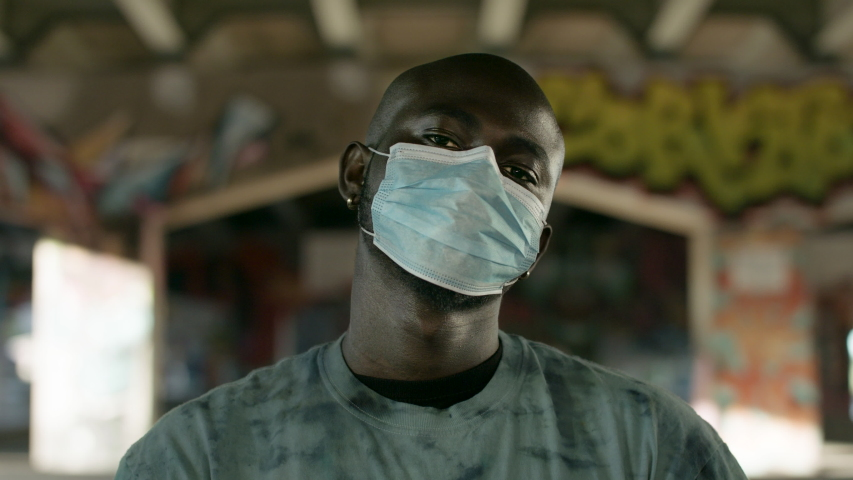 A portrait of a black man wearing a medical mask at an urban underpass. Shot in 4k.  | Shutterstock HD Video #1054332386