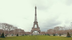 The Famous French Metal Eiffel Tower In Paris. European Romantic Symbol Of Love. Distance Shot. Ahead Is Green Grass And A Romantic Park. Day, Cloudy Weather