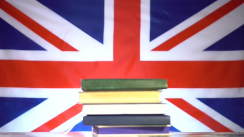 Cute student guy with glasses peeks out from a stack of books and smiles and slightly lowers his glasses from his face against the backdrop of the UK flag. Education in the UK. Education concept.