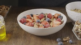 Slow video of pouring natural organic milk or yogurt into ceramic bowl with healthy granola and mix of fresh organic fruits and berries. Slow motion, 2K video, 240fps, 1080p.