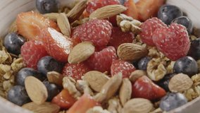 Process of preparing healthy breakfast or snack step by step from natural granola, fresh organic fruits and berries, mix of nuts in a ceramic bowl. Slow motion, 2K video, 240fps, 1080p.