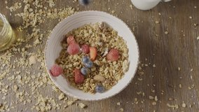 Video preparation of healthy breakfast or snack from falling ingredients natural granola, nuts and fresh ripe berries, fruits in a ceramic bowl on a wooden table. Slow motion, 2K video, 240fps, 1080p.