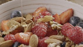 Slow video cooking healthy breakfast step by step - pouring natural organic honey into ceramic bowl with granola, nuts, mix of fresh organic fruits and berries. Slow motion, 2K video, 240fps, 1080p.
