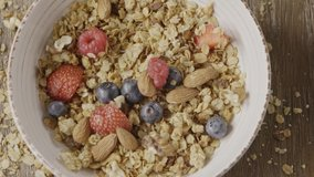 Top view process of preparation healthy breakfast or snack step by step from natural granola, fresh organic fruits and berries, mix of nuts in a ceramic bowl. Slow motion, 2K video, 240fps, 1080p.