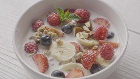 Freshly prepared healthy dieting breakfast from natural organic ingredients fruits, berries, granola and milk in a ceramic bowl and spoon is taking diet food. Slow motion, 2K video, 240fps, 1080p.