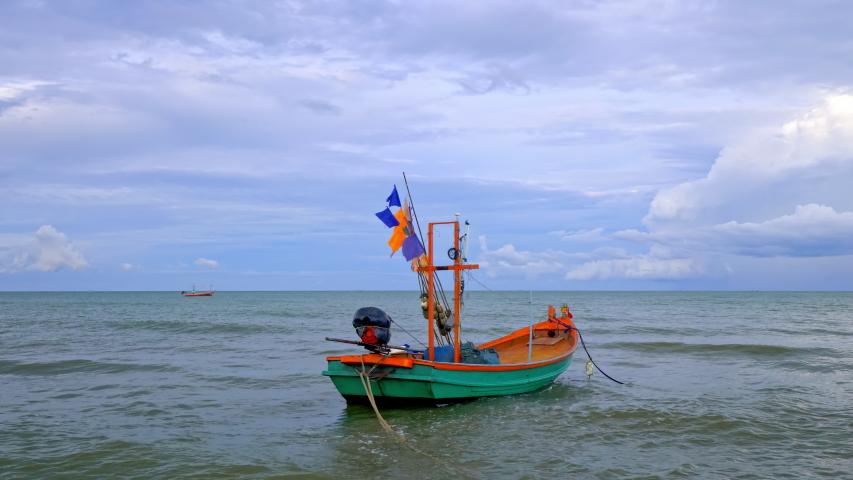 A small fishing boat anchored in the sea. | Shutterstock HD Video #1054342838