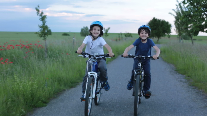 Children, boys, riding bikes  together summer time on a rainy day | Shutterstock HD Video #1054347365