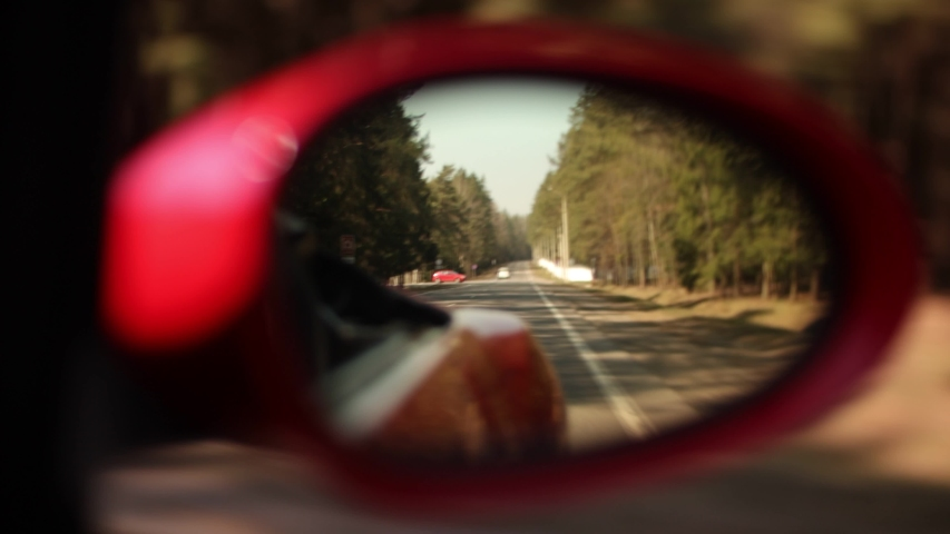 Video 4k red car in motion, the road is reflected in the long-distance mirror of the car