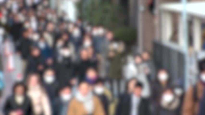 TOKYO, JAPAN -MARCH 2020 : Crowd of people walking down the street in morning rush hour. Many commuters going to work. People wearing mask to protect from Coronavirus (COVID-19) or cold. Blurred shot.
