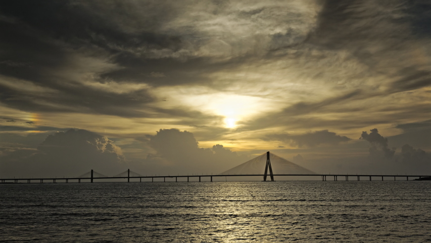 The Bandra-Worli Sea Link, also called Rajiv Gandhi Sea Link at sunset during pre monsoon weather. It is a cable-stayed vehicular bridge   Shutterstock HD Video #1054349078