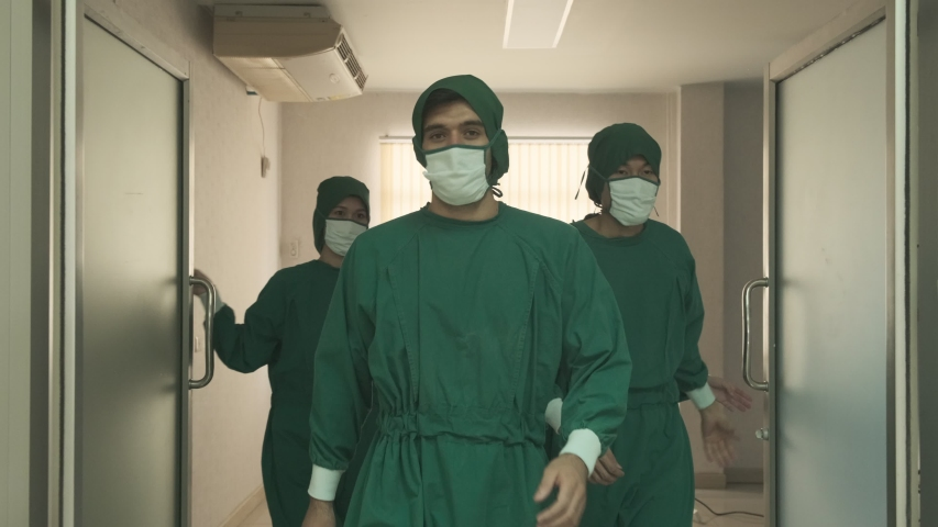 Group of doctors walking out the door from Hospital Operating Room with smile. Diverse Team, Multi ethnic of professional surgeons and nurses suture had successful surgery of covid19 patient operation Royalty-Free Stock Footage #1054351379