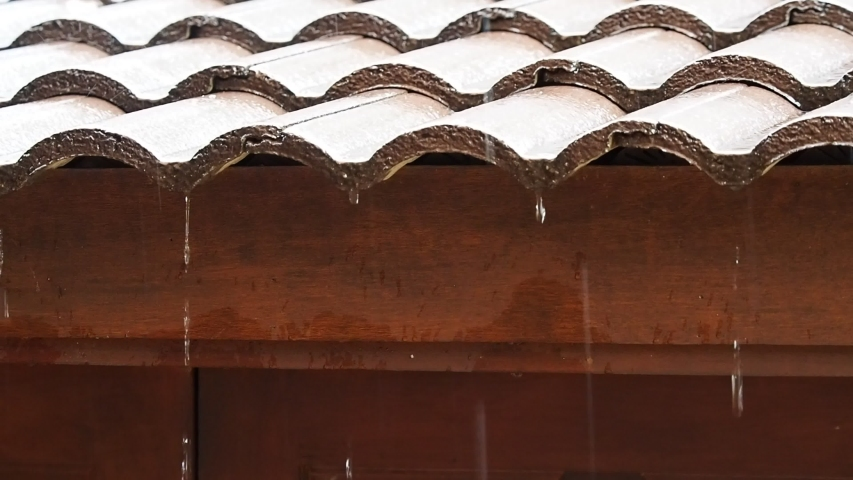 Rain water dropping from brown ceramic tile roof in day time.  Raining in motion.