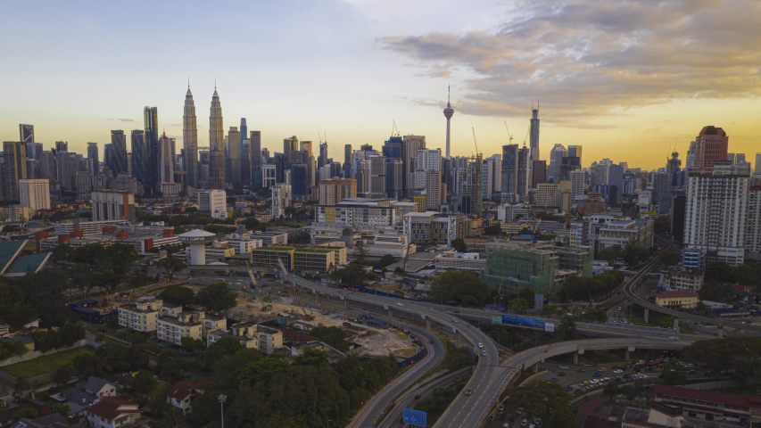 Malaysia Time lapse Sunset : Aerial city before dusk overlooking Kuala Lumpur city skyline and the Kuala Lumpur General Hospital with busy roundabout and streets. Prores UHD