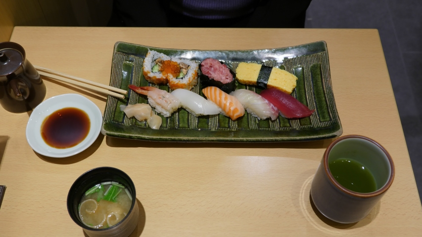 Assorted sushi on platter, tourist woman take cup with miso soup, top-down view of table at Japanese restaurant. Basic set meal served at affordable eatery in Tokyo | Shutterstock HD Video #1054354226